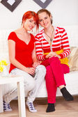 Two happy girlfriends sitting on sofa at living room — Stock Photo