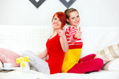 Two girlfriends sitting on sofa back to back and showing thumbs up gesture — ストック写真