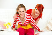 Cheerful girlfriends sitting on sofa and have fun — Stock Photo