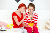 Attentive girl sitting on sofa and soothing her sad girlfriend — Stock Photo