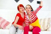 Funny girlfriends showing tongues while photographing themselves — Stock Photo