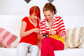Smiling girlfriends watching photos on photo camera — Stock Photo