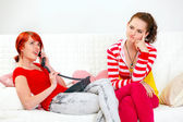 Bored girl sitting on sofa while her girlfriend phone talking — Stock Photo