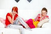 Novias jóvenes sentados en el sofá y hablando por teléfonos móviles — Foto de Stock