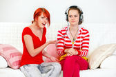 Sitting on sofa indignant girl pointing on her girlfriend listening somethi — Stock Photo