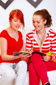 Cheerful girlfriends sitting on sofa and looking fashion magazin — Stock Photo