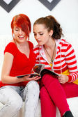Interested girlfriends sitting on sofa and looking fashion magazine — Stock Photo