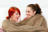 Two smiling girlfriends sitting on sofa wrapped up in plaid — Stock Photo