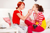 Smiling girl applying lipstick to her girlfriend — Stock Photo