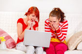 Laughing girlfriends looking on laptop — Stockfoto