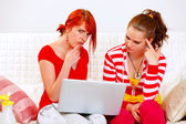 Bewildered girlfriends looking in laptops screen — Stock Photo