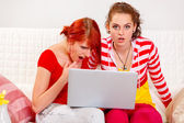 Two girlfriends amazed the seen in a laptop — Stock Photo
