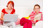 Pretty girl bored while her girlfriend using laptop — Stock Photo