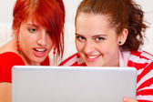 Funny girlfriends using laptop. Closeup — 图库照片