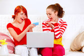 Two smiling girlfriends making purchase using credit card — Stock Photo