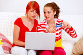 Two pretty girlfriends shopping in net using credit card — Stock Photo