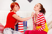 Cheerful girl applying new perfume on her girlfriend — Stock Photo