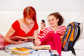 Responsible girl studying while her girlfriend reading sms — Stock Photo