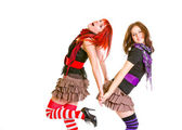 Two pretty cheerful girls standing back to back and holding hands — Foto Stock