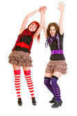 Two cute happy girlfriends standing with hands raised up — Stock Photo