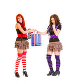 Caring cute girl giving one shopping bag her surprised girlfriend — Stock Photo