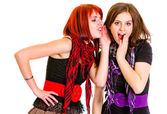 Girl whispering gossips in ear her surprised girlfriend — Stock Photo