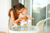 Young mama feeding look aside little baby at terrace — Foto de Stock