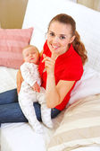 Happy mother holding sleeping baby and showing shhh gesture — Stock Photo