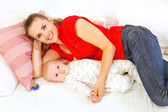Happy mother and baby laying on sofa — Stock Photo