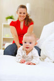 Smiling mother and adorable baby playing on sofa — Stock Photo