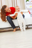 Smiling mother helping cheerful baby learn to walk — Stock Photo