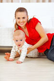 Happy mother and lovely baby playing on floor — Stock Photo