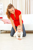 Smiling mother helping cheerful baby learn to creep — Stock Photo