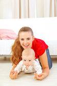 床で遊ぶ愛らしい赤ちゃんとママの笑顔 — ストック写真