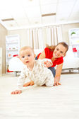 Smiling mommy playing with creeping on floor baby — Stock Photo