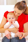 Baby putting his hands in mouth while sitting on mother laps — Stock Photo
