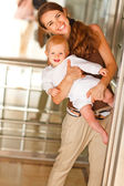 Portrait of smiling mother with baby looking out from elevator — Stock Photo