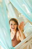 Smiling woman looking out from curtain — Photo