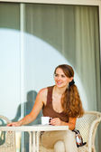 Female sitting on terrace with cup of coffee and looking in corner — Stock Photo