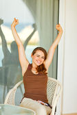 Beautiful woman sitting on terrace and stretching after relaxing — Stock Photo