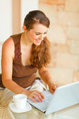 Smiling young woman with cup of coffee working on laptop on terr — Stock Photo