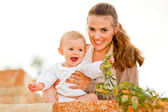 Portrait of happy mother and laughing baby playing with plants — Stock Photo