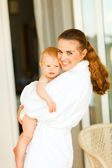 Portrait of young mother in bathrobe with baby in hand — Стоковое фото