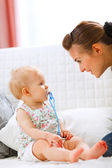 Lovely baby and young mother playing on sofa — ストック写真