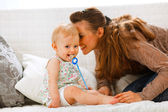 Adorable baby with soother and young mother playing on divan — Stock Photo