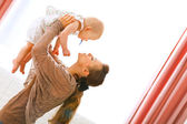 Young mama playing with baby by rising her up — Stock Photo