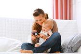 Młoda matka i dziecko uśmiechający się wyglądający zdjęcia w aparacie — Zdjęcie stockowe