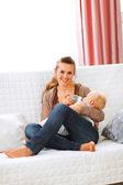 Joven madre sentada en el sofá y alimentando a su bebé — Foto de Stock