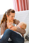 Young mother sitting on sofa and feeding her baby — Stock Photo