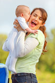 Baby kissing holding her happy mother — Stock Photo
